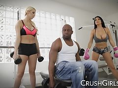 Kenzie with an increment of Romi share a big black cock at the gym
